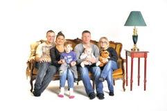 Lek för två ung familjer som dumbommen med ett barn sitter på en soffa royaltyfria foton