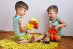 Lek för tvilling- bröder med dockor Royaltyfri Bild