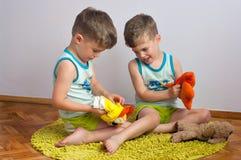 Lek för tvilling- bröder med dockor Arkivbild
