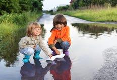 Lek för tre pojke i pöl Royaltyfri Foto