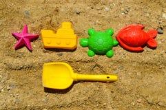 Lek i den sandiga stranden - plast-diagram och en skulderblad royaltyfri bild