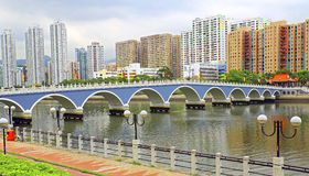 Lek yuen bridge of shatin, hong kong. Arc shaped lek yuen bridge over shing mun river and housing estates along shatin, hong kong Royalty Free Stock Photography