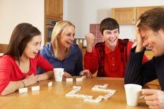 Leka domino för familj i kök Royaltyfria Bilder