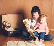 leka för barn Pojke i pilot- hjälm med den plana modellen och suitc Fotografering för Bildbyråer
