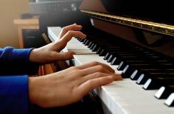 leka för barnpiano Nära övre sidosikt av unga händer och fingrar som spelar en sång royaltyfri bild