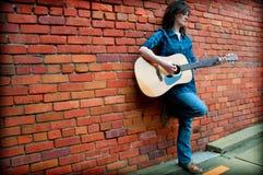 leka för brunettkvinnliggitarr Royaltyfri Fotografi