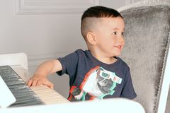 leka för pojkepiano royaltyfria foton