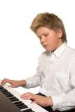 leka för pojkepiano Arkivbilder