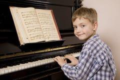 leka för pojkepiano royaltyfria bilder