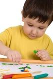 leka för pojkeplasticine Arkivbilder