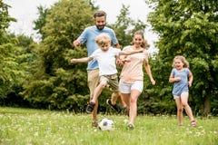leka fotboll för familj arkivbild