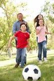 Leka fotboll för familj i park Royaltyfria Foton