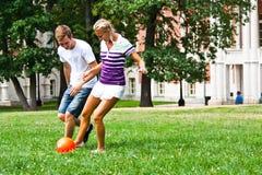 Leka fotboll för man och för kvinna arkivfoton