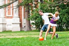 Leka fotboll för man och för kvinna Royaltyfri Bild