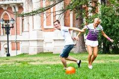 Leka fotboll för man och för kvinna arkivbild