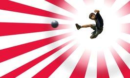 leka fotboll för pojkeclippingbana arkivfoto