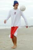 leka fotboll för strandpojke Arkivbilder