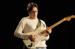 Leka gitarr för musiker i lvekonsert royaltyfri fotografi