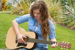 Leka gitarr för tonårs- flicka Arkivfoton