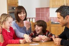 Leka kort för familj i kök Arkivfoto