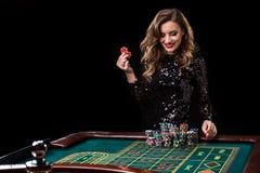 leka kvinna för kasino Kvinnainsatshögar av chiper som spelar rou Arkivfoton
