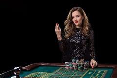 leka kvinna för kasino Kvinnainsatshögar av chiper som spelar rou Arkivbild