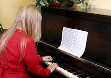 leka kvinnabarn för piano Arkivfoto