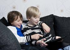 Leka med en tablet Fotografering för Bildbyråer