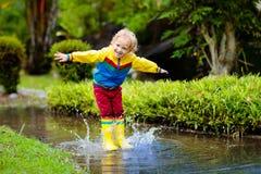 leka p?l f?r barn Ungar hoppar i höstregn royaltyfria bilder