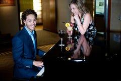 Leka piano för man och underhålla hans följe Royaltyfria Bilder