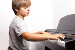 Leka piano för ung pojke Royaltyfria Bilder