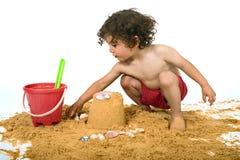 leka sand för pojke Arkivbilder