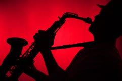 leka saxofonsilhouette för man Royaltyfria Bilder