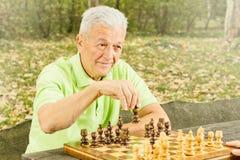 Leka schack för gammalare man Royaltyfria Bilder
