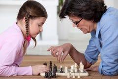 Leka schack med mormor royaltyfria bilder