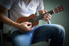 leka ukulele för man royaltyfri bild