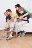 Leka videogames för ung familj Fotografering för Bildbyråer