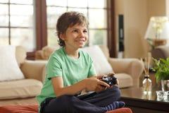 Leka videospel för gullig pojke Arkivfoton