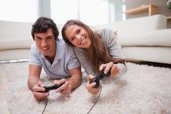 Leka videospel för par på golvet Arkivfoto