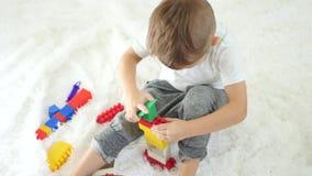 Lekar för ett barn med färgkvarter som sitter på en vit bakgrund Den lyckliga pojken spelar Begreppet av barns utveckling arkivfilmer
