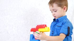 Lekar för lekar för ett småbarn med färgkvarter av formgivaren Passiva lekar av barn utveckling Stående av en pojke arkivfilmer