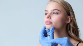 Lekarek ręki z strzykawką i żeńską piękną twarzą Młoda powabna kobieta ma procedurę powiększanie wargi zbiory wideo