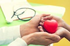 Lekarek r?ki trzyma czerwonego masa?u serce i daje cierpliwi ma?e dzieci dla odzyskuj? od choroby Szpital i opieka zdrowotna zdjęcia stock
