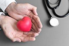 Lekarek r?ki trzyma i daj? czerwonemu masa?u sercu pacjent dla odzyskuj? od choroby Szpital i opieki zdrowotnej poj?cie CPR i zdjęcie stock