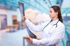 Lekarek spojrzenia przy promieniowanie rentgenowskie wizerunkami na kliniki sali tle zdjęcia royalty free