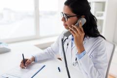 Lekarka dzwoni na telefonie przy szpitalem z schowkiem Zdjęcie Royalty Free