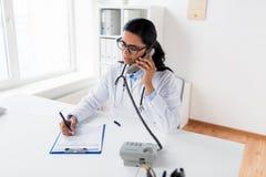 Lekarka dzwoni na telefonie przy szpitalem z schowkiem Fotografia Royalty Free