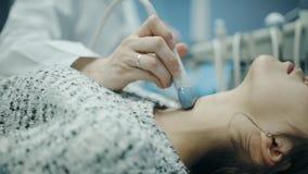 Lekarka egzamininuje dziewczyny ` s gardło z specjalnym wyposażeniem zbiory
