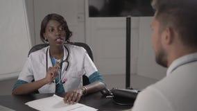 Lekarka Egzamininuje męskiego pacjenta W biurze W Białym żakiecie, ciśnienie krwi, amerykanina afrykańskiego pochodzenia czerni p Zdjęcia Royalty Free
