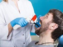Lekarka egzamininuje oralnego zagłębienie na zębu gniciu Próchnicy ochrona Zębu gnicia traktowanie Dentysta pracuje z stomatologi zdjęcie stock